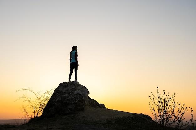 Silhouette d'une femme randonneur debout seul sur une grosse pierre au coucher du soleil dans les montagnes.