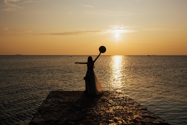 Silhouette d'une femme regarde le coucher du soleil sur une mer ou un océan.