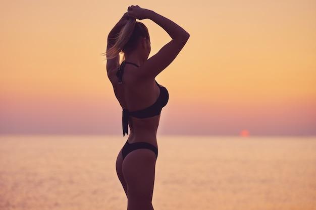Silhouette de femme sexy posant au lever du soleil sur la plage