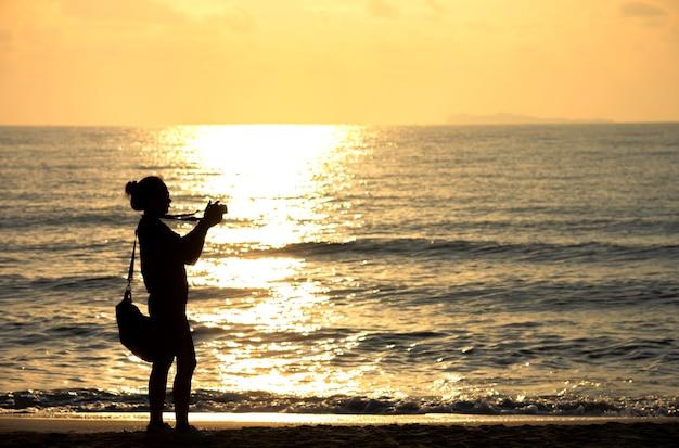 Silhouette d'une femme tenant un appareil photo et sac de transport fond coucher de soleil doré lumière matin réflexion mer.