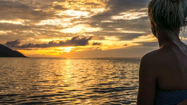 Silhouette de femmes jung dans la lumière chaude du coucher du soleil, l'île de kri. raja ampat, indonésie, papouasie occidentale.