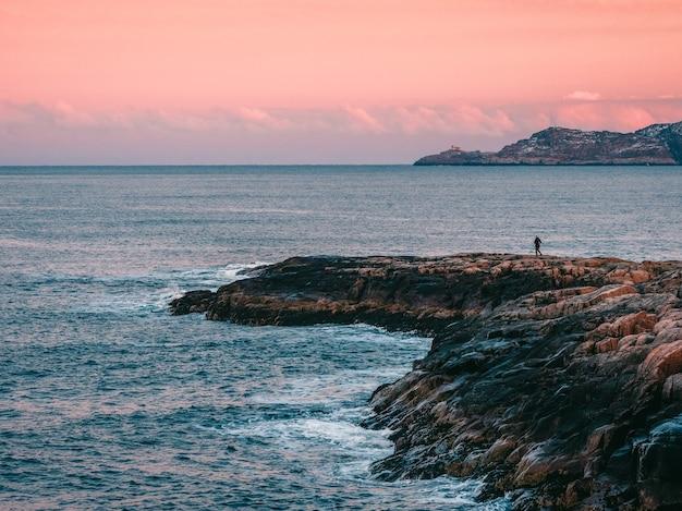 Une silhouette, une figure sur une falaise abrupte en arrière-plan