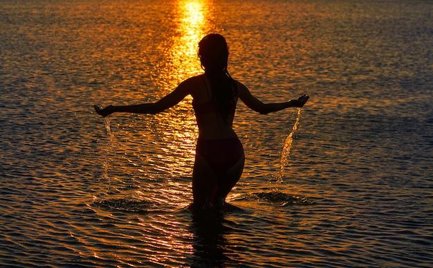Silhouette de fille au coucher du soleil à la plage, bras ouverts