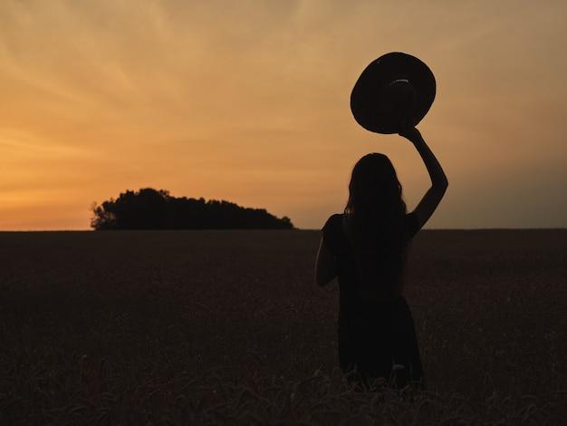 Silhouette d'une fille avec un chapeau dans un champ au coucher du soleil