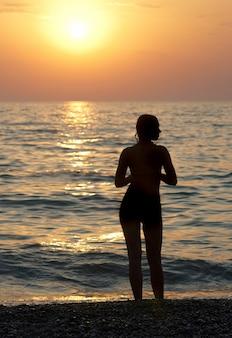 Silhouette de fille et coucher de soleil sur la mer