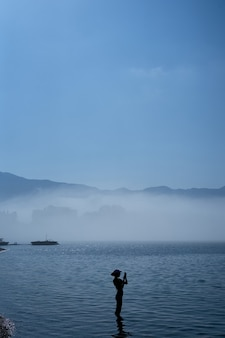 Silhouette d'une fille debout dans la mer et prenant des photos au téléphone