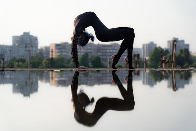 Silhouette de fille flexible et en forme pliant son dos concept de yoga et de mode de vie sain