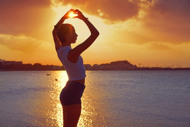 Silhouette de fille en forme de coeur de coucher de soleil plage
