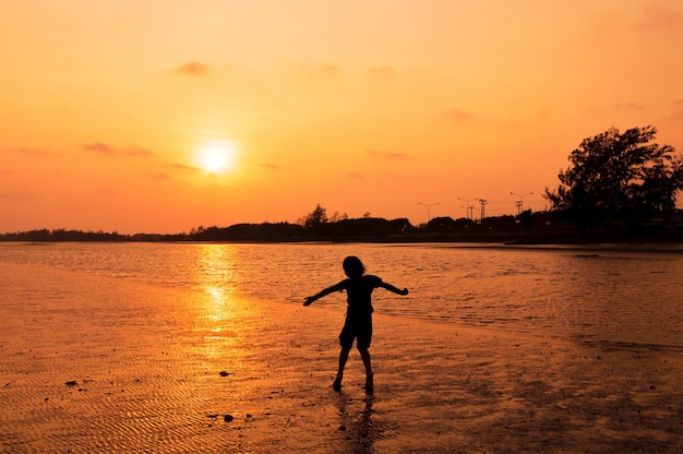 Silhouette de fille jouant sur la plage au coucher du soleil