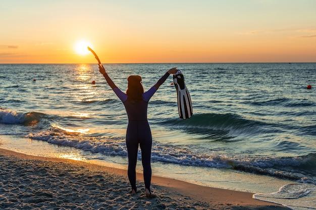 Silhouette d'une fille plongeur dans une combinaison avec des palmes et un tuba dans ses mains