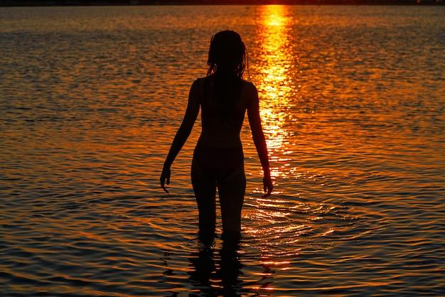 Silhouette de fille à la recherche du coucher de soleil sur la plage