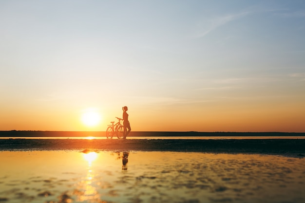La silhouette d'une fille sportive en costume debout près d'un vélo dans l'eau au coucher du soleil par une chaude journée d'été. notion de remise en forme.
