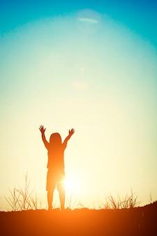 La silhouette de garçon au coucher du soleil