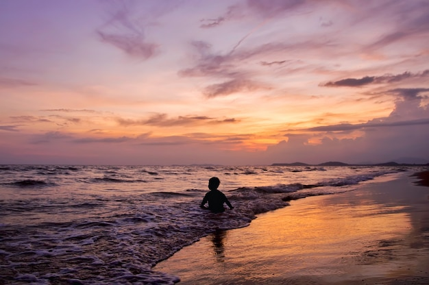 Silhouette d'un garçon jouant sur la plage au coucher du soleil