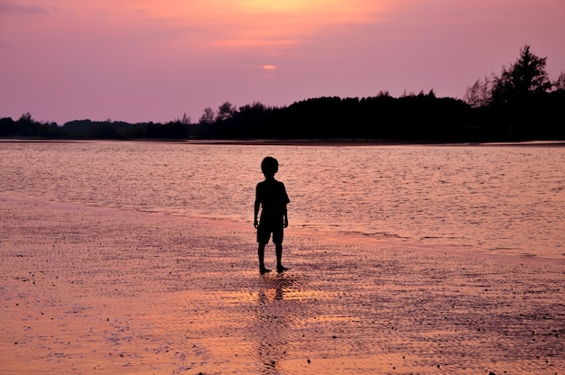 Silhouette d'un garçon solitaire debout sur la plage au coucher du soleil