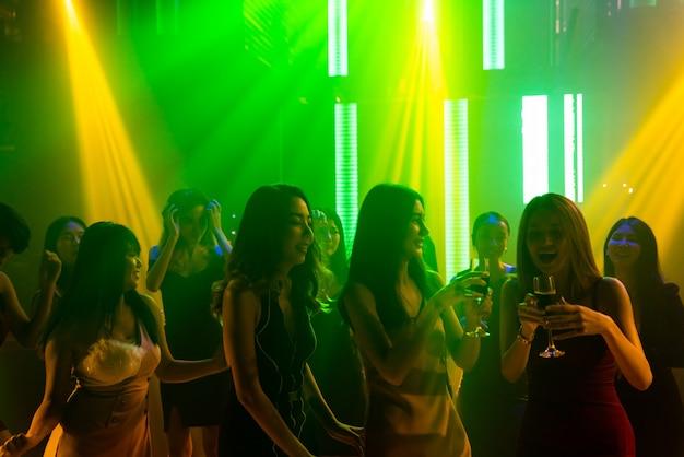Silhouette de gens dansent dans une discothèque sur la musique du dj sur scène