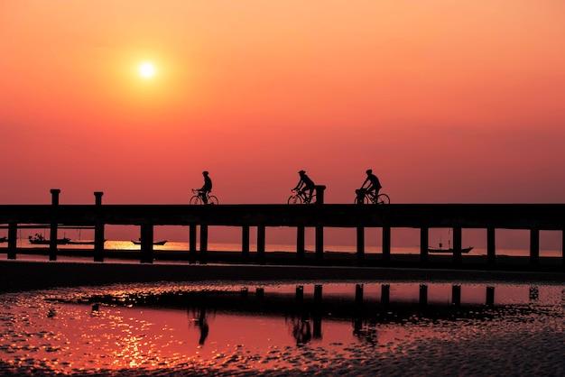 Silhouette les gens font du vélo dans la lumière du soir du ciel
