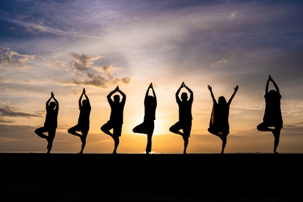 Silhouette, de, gens groupe, faire, yoga, pendant, coloré, coucher soleil, ou, lever soleil, plage