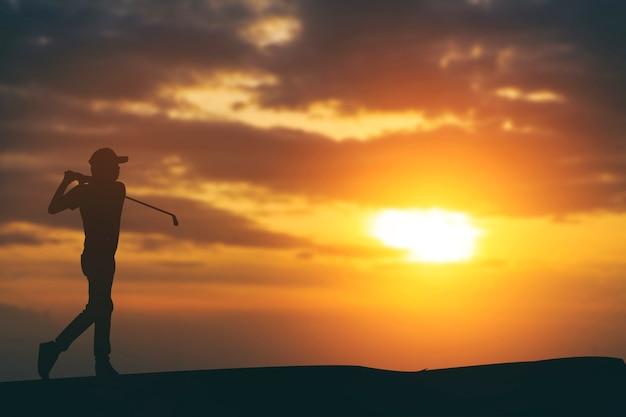 Silhouette de golfeurs frappant balayer et garder le terrain de golf en été pour détendre le temps.