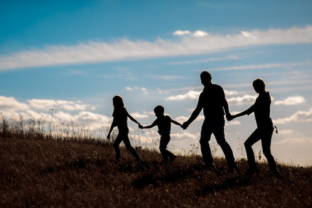 Silhouette, groupe, de, famille heureuse, jouer, sur, pré, coucher soleil, summertime