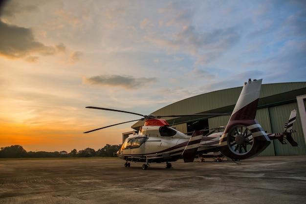 Silhouette d'hélicoptère dans le stationnement ou piste avec fond de lever de soleil