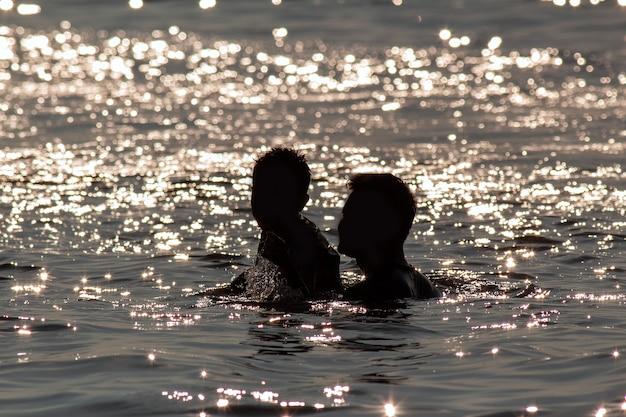 Silhouette heureux père et fils jouant dans l'eau