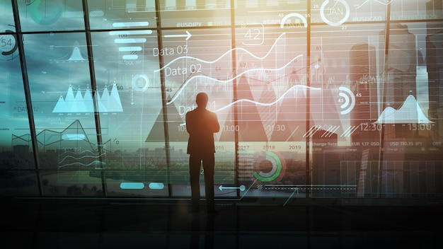 Silhouette d'homme d'affaires dans un bureau sombre devant un large éventail d'infographies