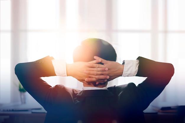 Silhouette d'homme d'affaires a mis sa main sur la tête par la fenêtre de bureau avec la lumière du soleil.