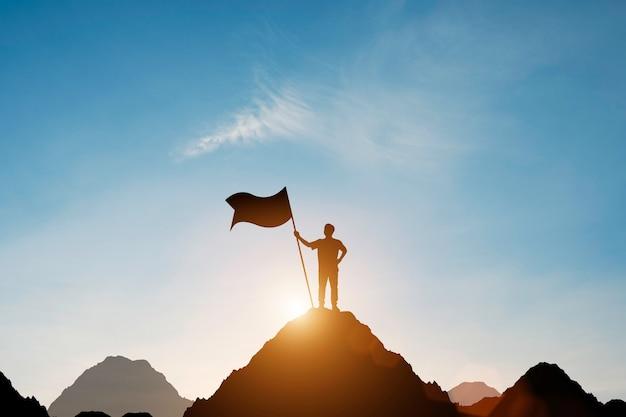 Silhouette d'homme d'affaires tenant le drapeau au sommet de la montagne avec plus de ciel bleu et la lumière du soleil.