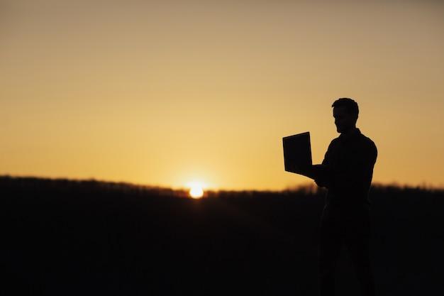 Silhouette d'homme d'affaires travaillant avec un ordinateur portable au coucher du soleil