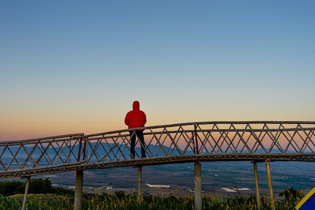 Silhouette d'un homme asiatique debout sur un pont en bambou à ban doi sa-ngo chiangsaen, province de chiang rai, thaïlande.