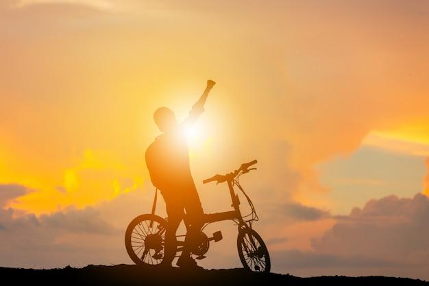 Silhouette d'un homme assis sur un vélo avec une main levée au coucher du soleil