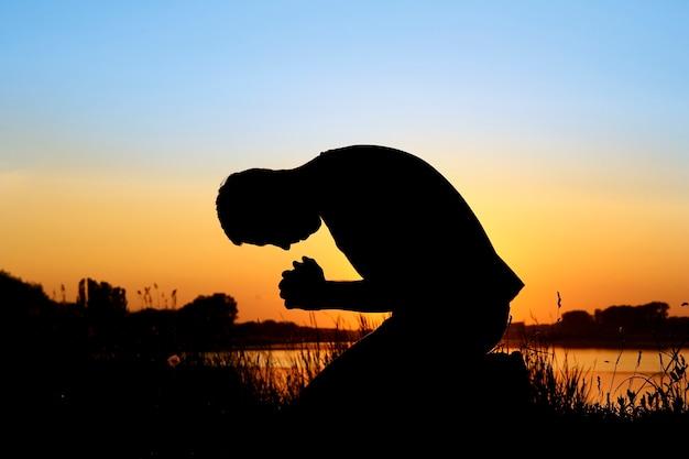Silhouette sur l'homme au coucher du soleil priant dieu