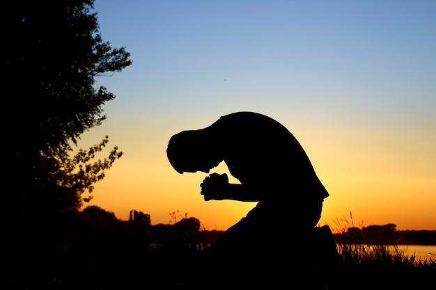 Silhouette sur l'homme au coucher du soleil priant