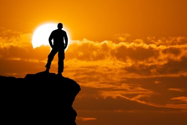 Silhouette d'homme au sommet de la montagne