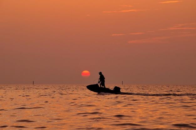 Silhouette de l'homme au volant de jetski sur la mer avec pendant le coucher du soleil