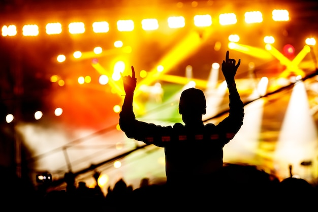 Silhouette d'homme aux mains levées sur concert. foule sur spectacle de musique