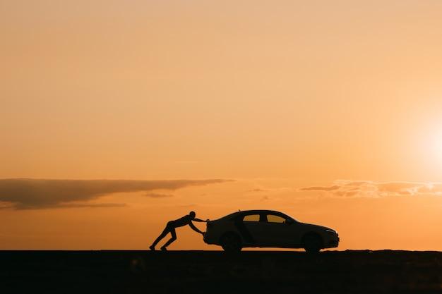 Silhouette d'homme conducteur poussant sa voiture sur une route vide après une panne au coucher du soleil,
