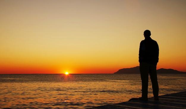 Silhouette d'homme sur le coucher du soleil sur la jetée de la mer