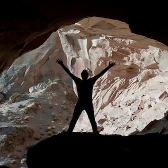 Silhouette d'un homme debout avec les bras levés dans la grotte d'ulrike, amangiri, canyon point, utah, états-unis