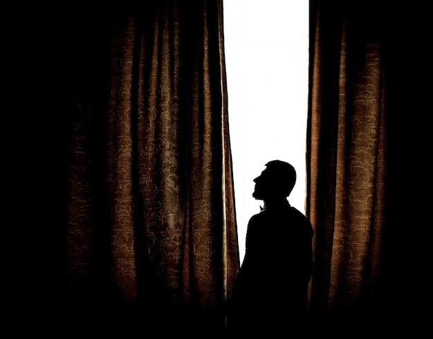 Silhouette d'un homme debout devant une fenêtre lumineuse