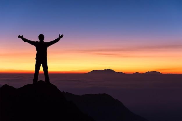 Silhouette de l'homme debout et répandre la main sur le sommet de la montagne pour profiter du ciel coloré.