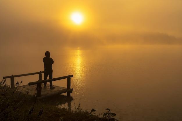 Silhouette homme déprimé debout sur le lac de la rivière houseboat