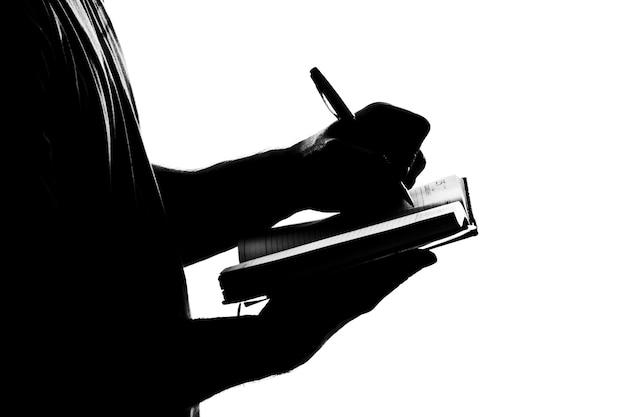 Silhouette d'homme écrit le journal d'affaires. isolé sur blanc