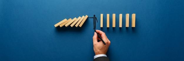 Silhouette d'un homme faisant un geste d'arrêt pour empêcher les dominos en bois de s'effondrer