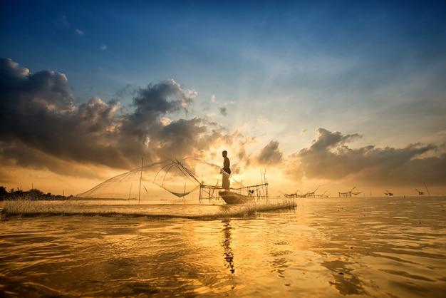 Silhouette d'homme avec des filets de pêche le matin à pakpra, phatthalung, thaïlande