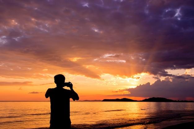 Silhouette d'homme garder des souvenirs avec le téléphone appareil photo dans sa main