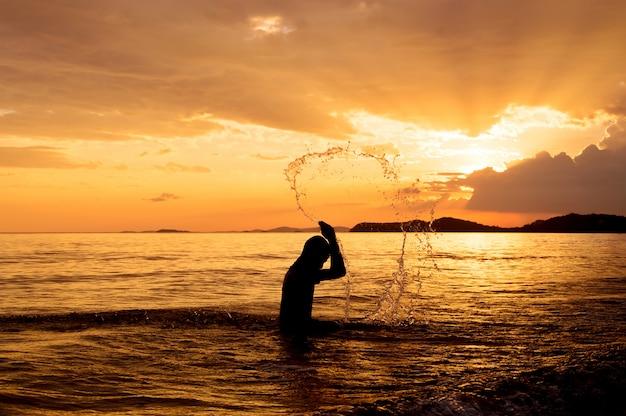 Silhouette d'un homme heureux jouant sur la plage au coucher du soleil