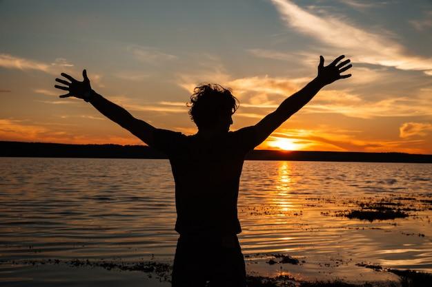 Silhouette d'homme heureux avec les mains sur le fond du coucher du soleil à la plage