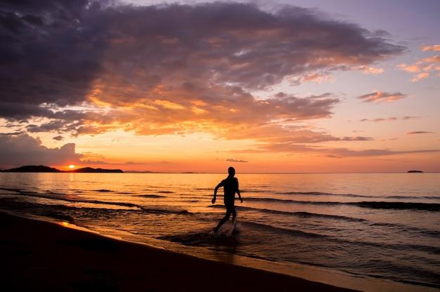 Silhouette d'un homme heureux qui court sur la plage au coucher du soleil